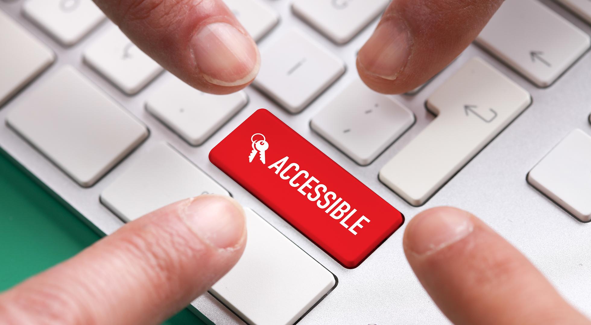 Dita che indicano un tasto rosso di una tastiera con la scritta accessible