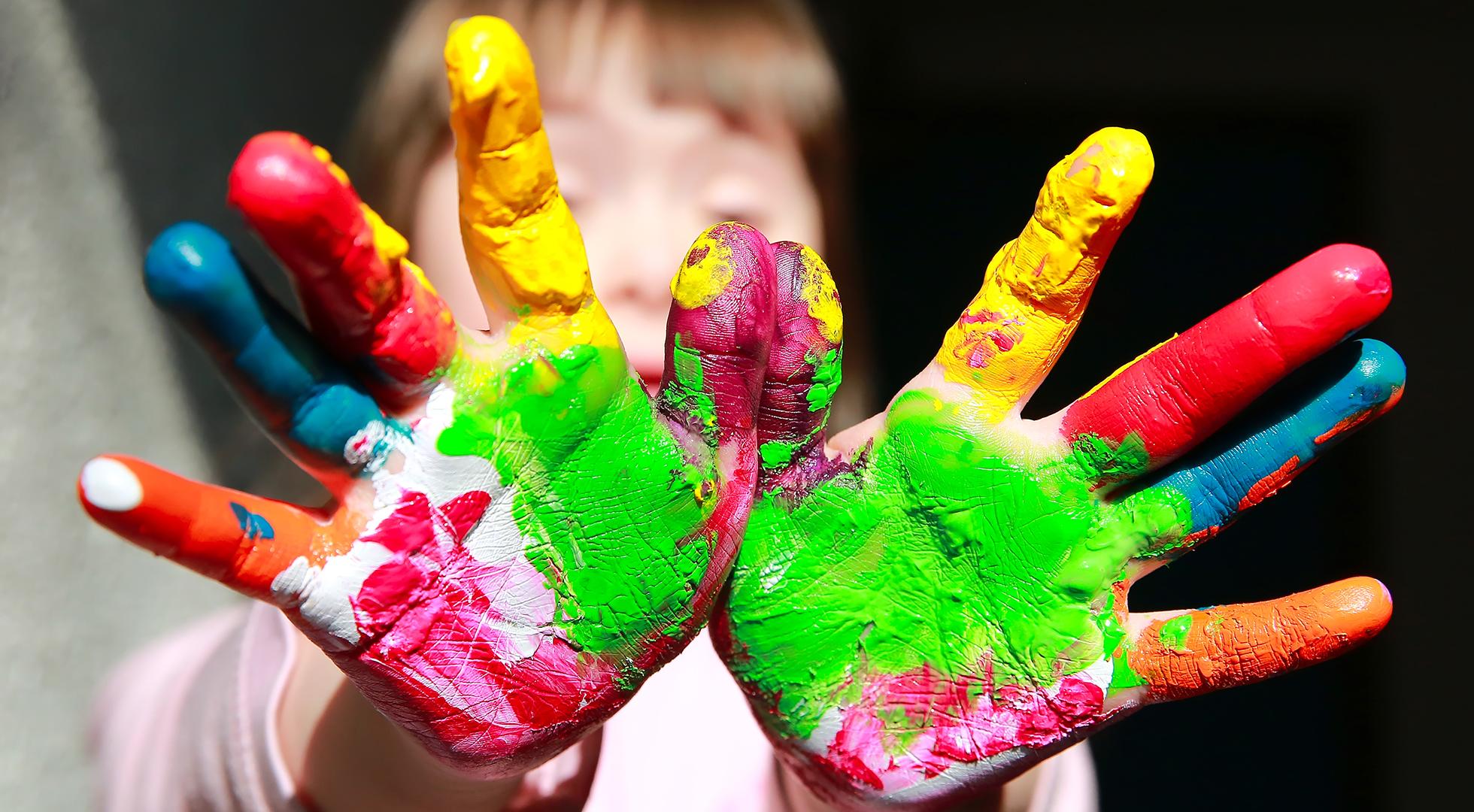 Bambina affetta da Sindrome di Down che gioca con la pittura