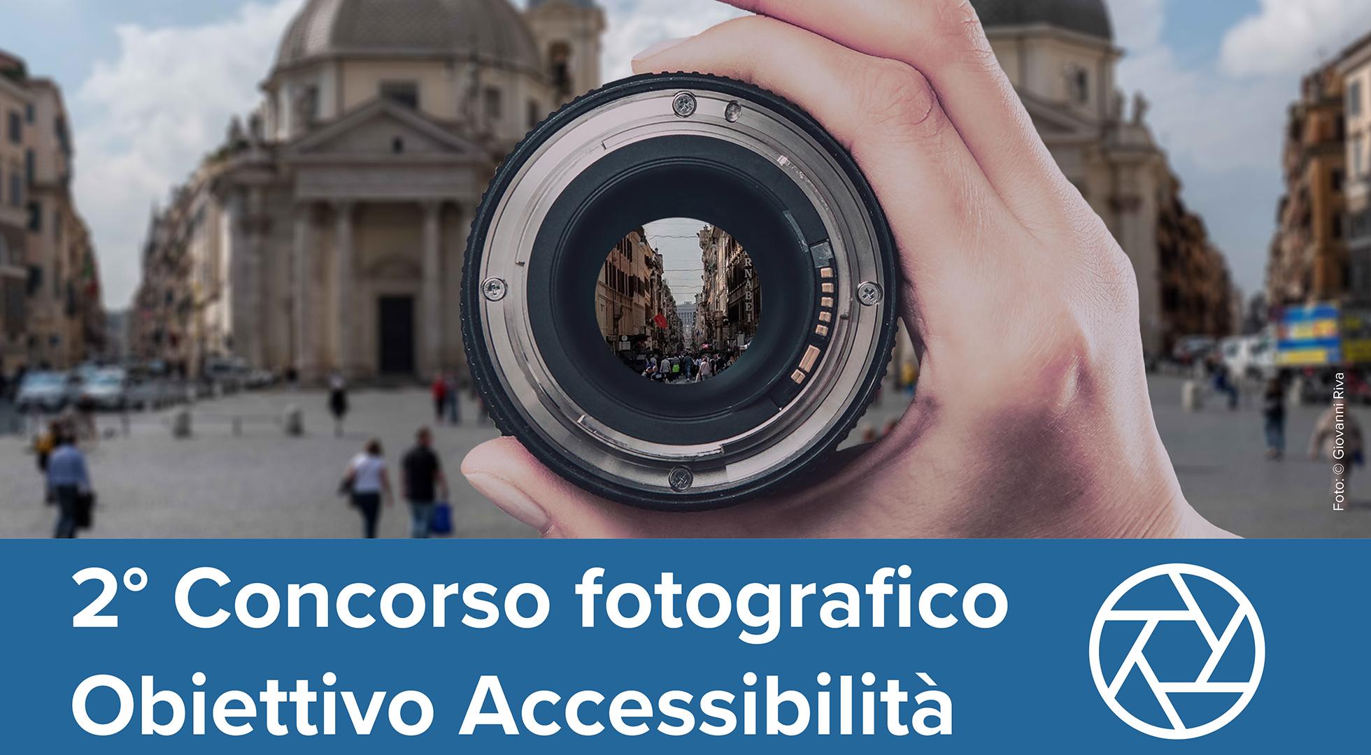 """Foto ufficiale del concorso """"Obiettivo accessibilità"""". Una mano che tiene un obiettivo puntato su Via del Corso a Roma"""